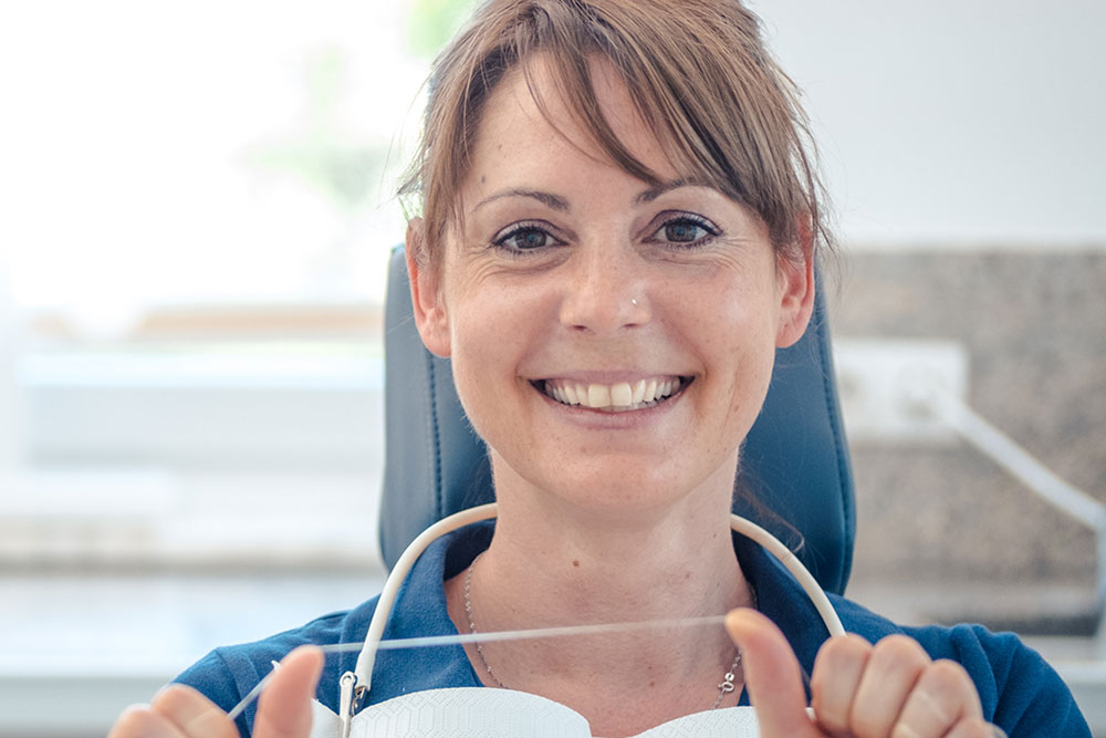 Zahnarztangst Giesing - Dr. Koenigsfeld - Frau mit Zahnseide auf Behandlungsstuhl