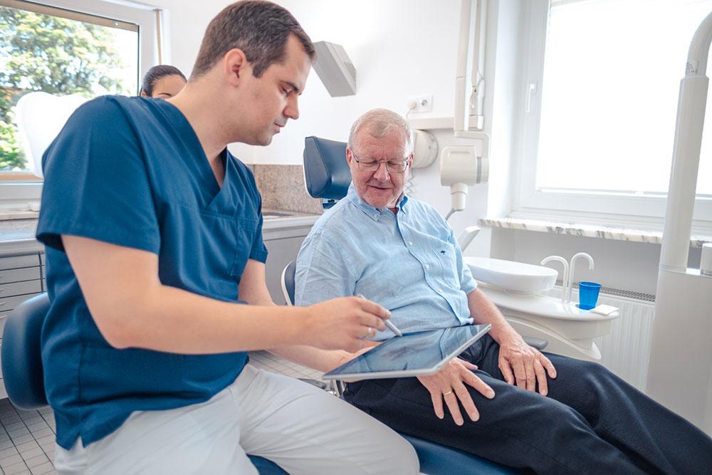 Zahnarzt Giesing - Dr. Koenigsfeld & Kollegen - einfühlsame Erläuterungen der Behandlung für einen älteren Herren auf dem Zahnarztstuhl